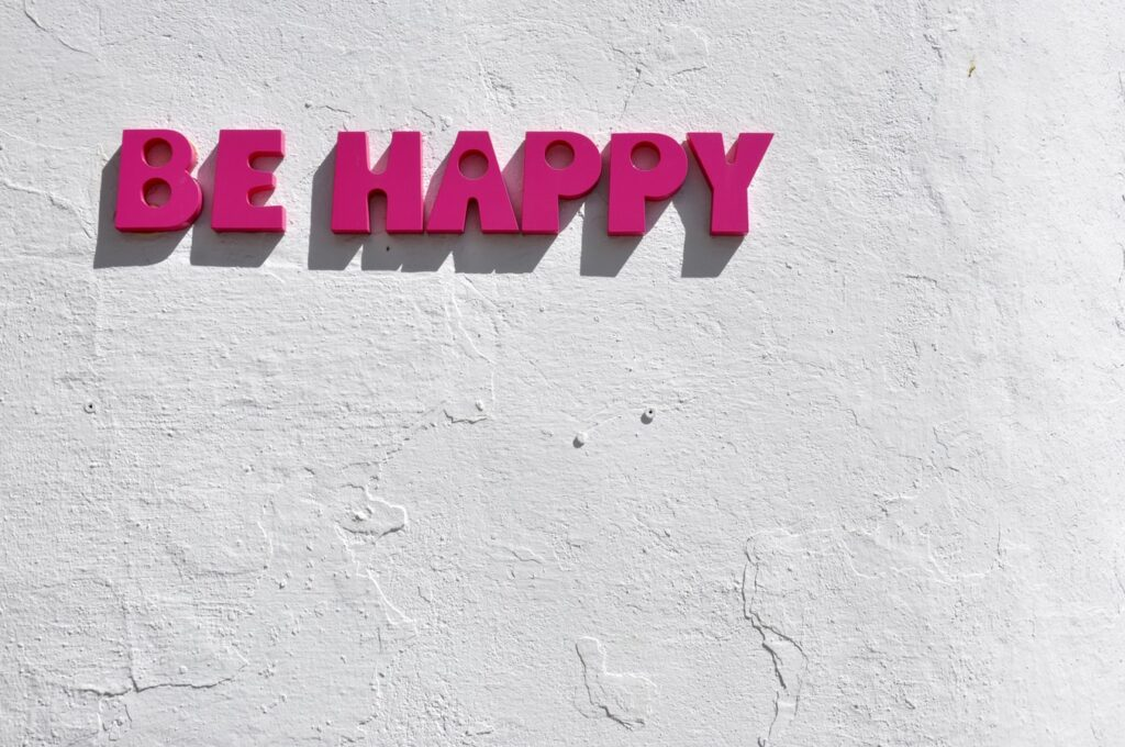 "the words ""Be happy"" written on a wall showing Example of Positive mindset or toxic positivity"