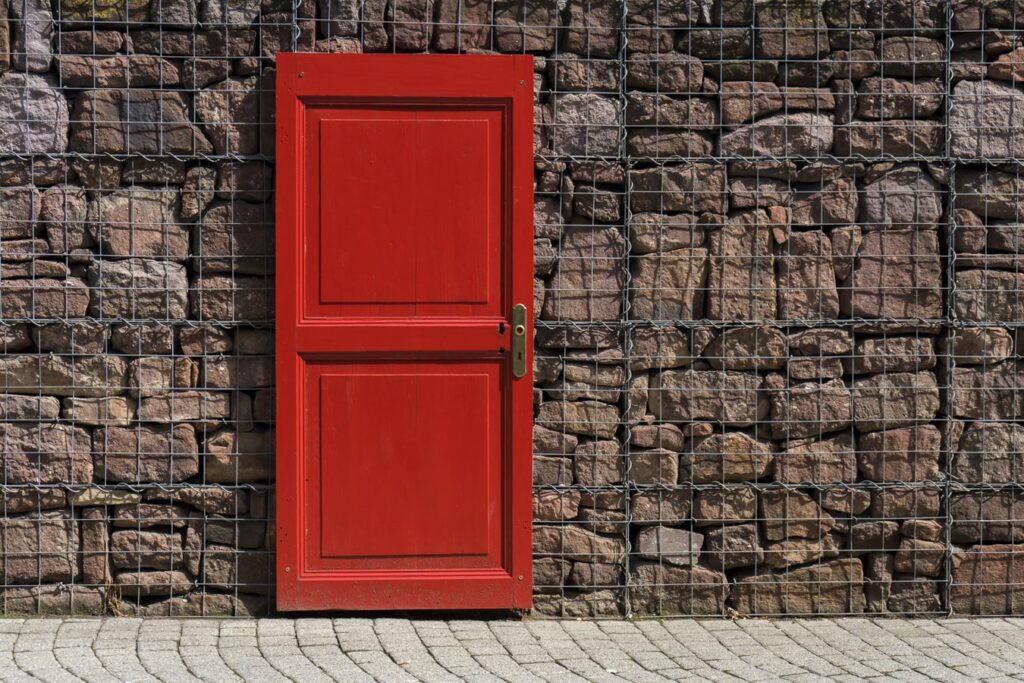 A red door against a caged brick wall symbolizing a closed fix mindset.