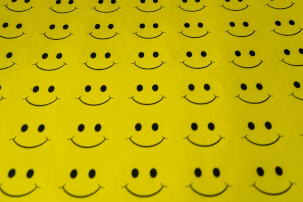 Rows of yellow smiley face stickers symbolizing the fake smiles of toxic positivity