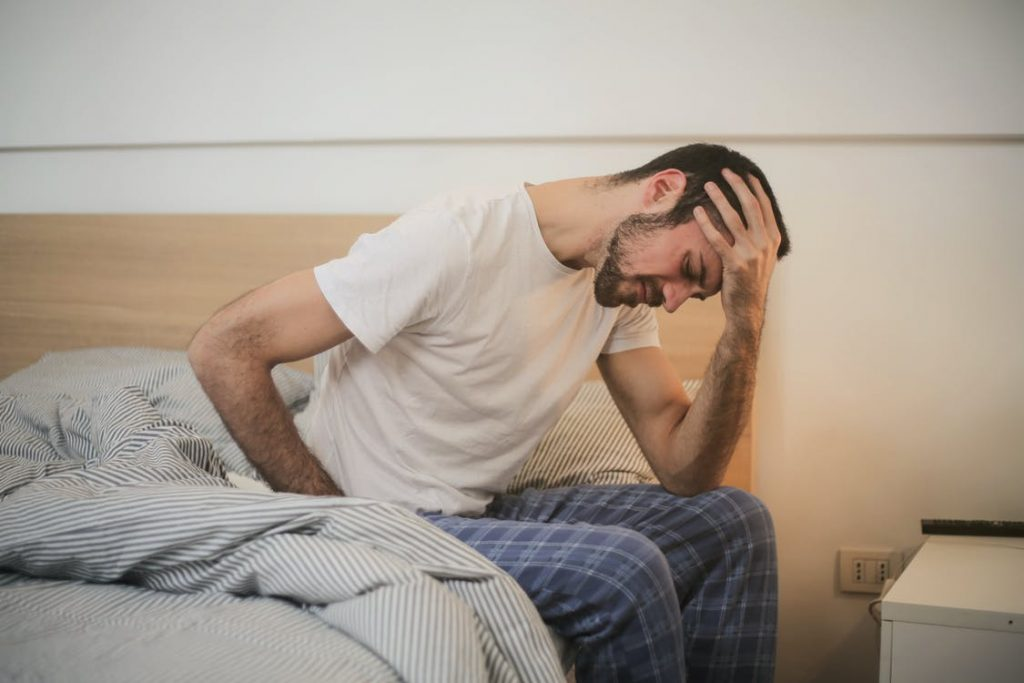 Man sitting at the edge of the bed looking like he is in pain