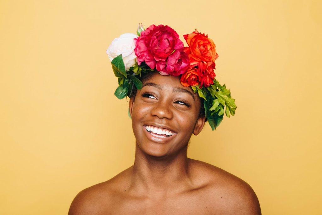 Black women smiling with a floral crown