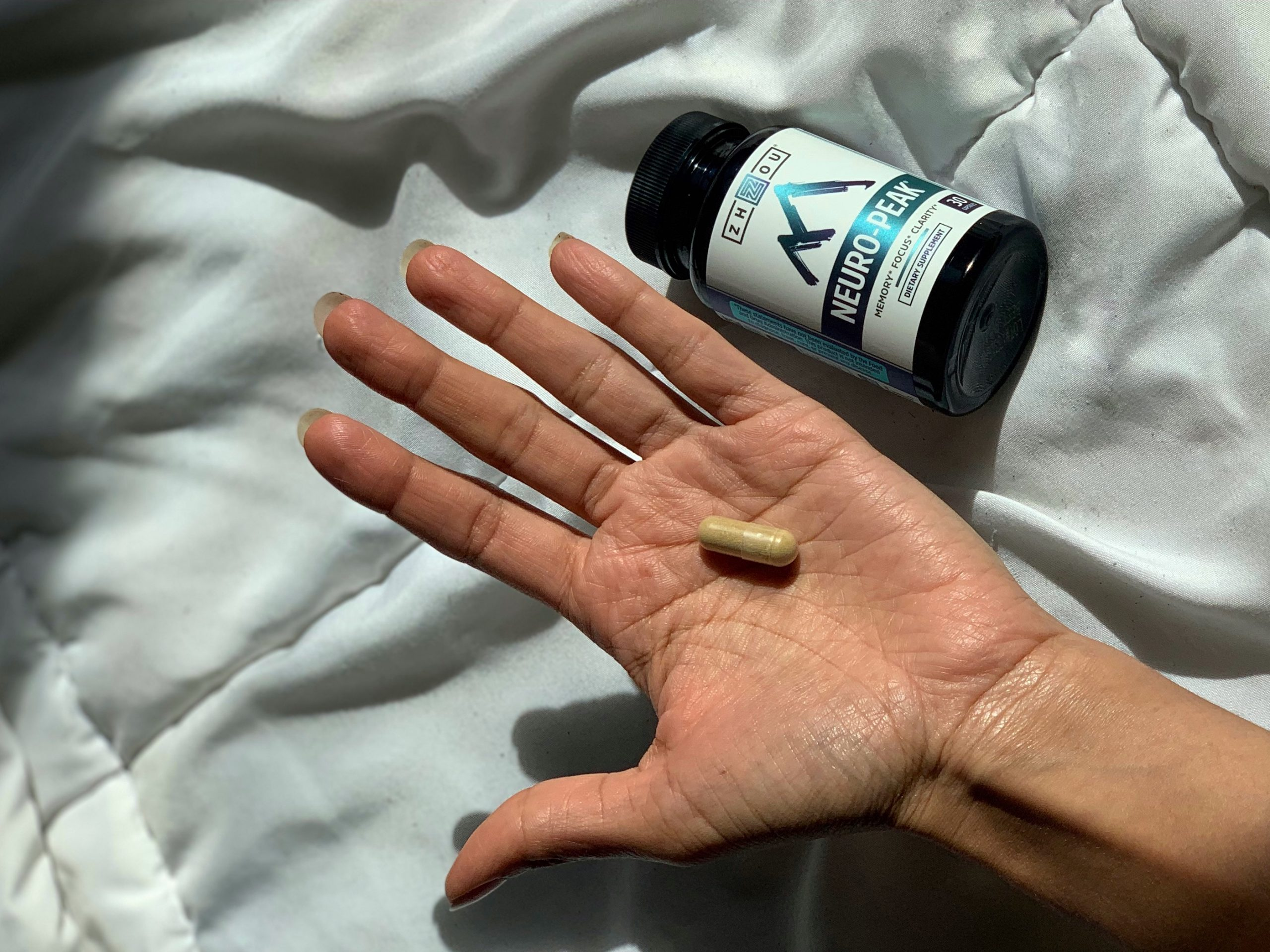 Herbal supplement in a hand Neuro Peak on a bed with white comfy sheets a nootropic for cognitive health.