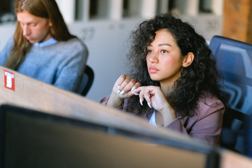 Women of color with curly hair at work looking off into the distance in deep thought