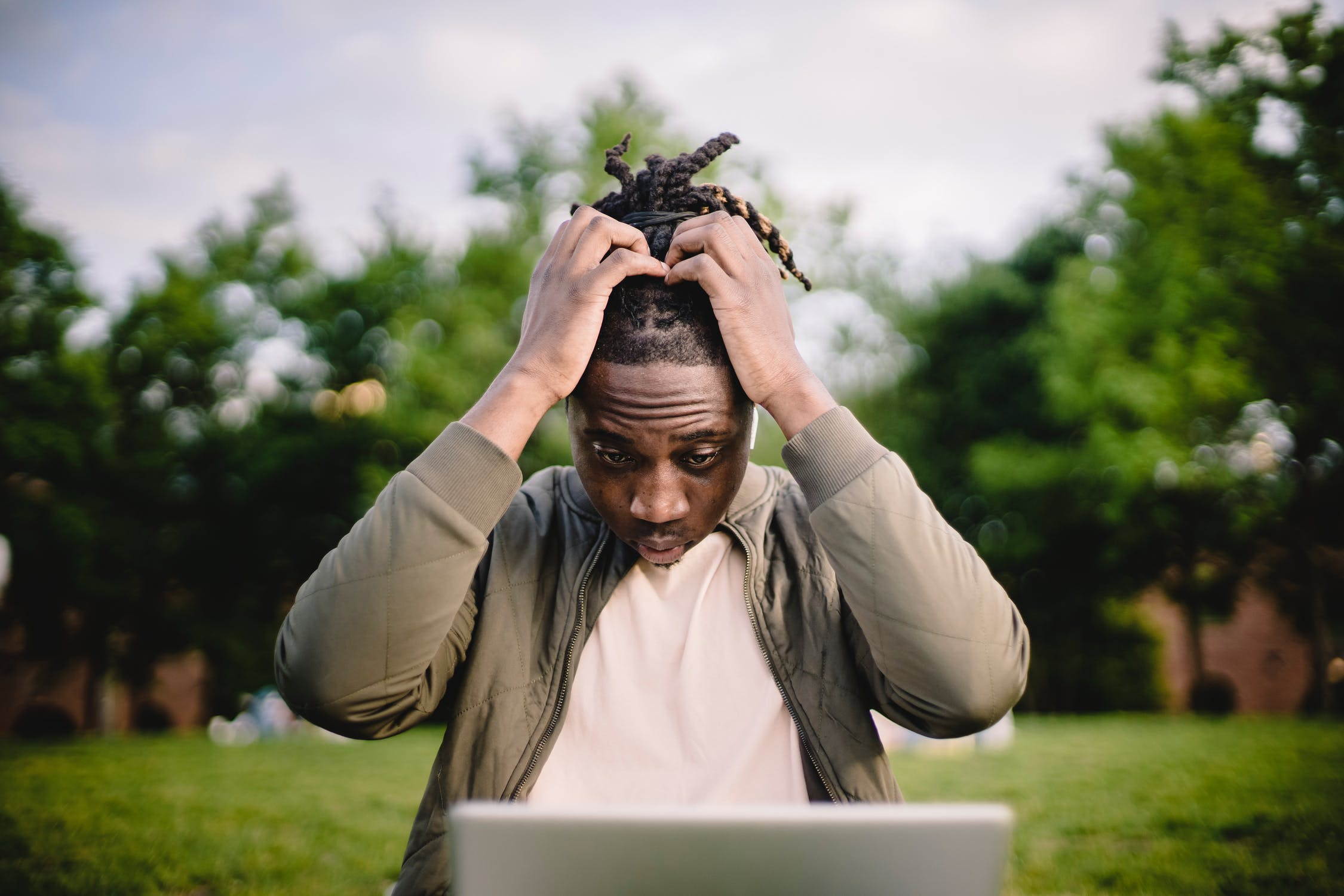 Black man with dread locks looking at his computer with his hands on his head looking overwhelmed and stressed showing signs of poor brain health and the need for a nootropic for cognitive health.
