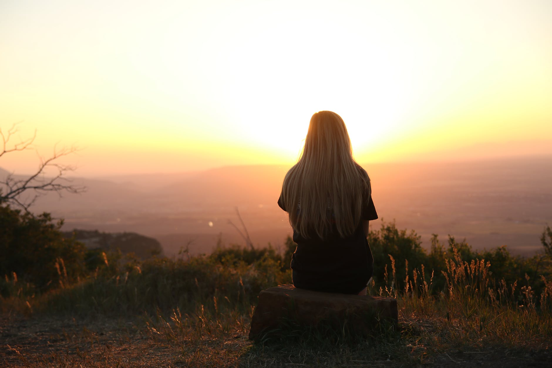woman looking at sunset realizing that It's okay to feel unaccomplished