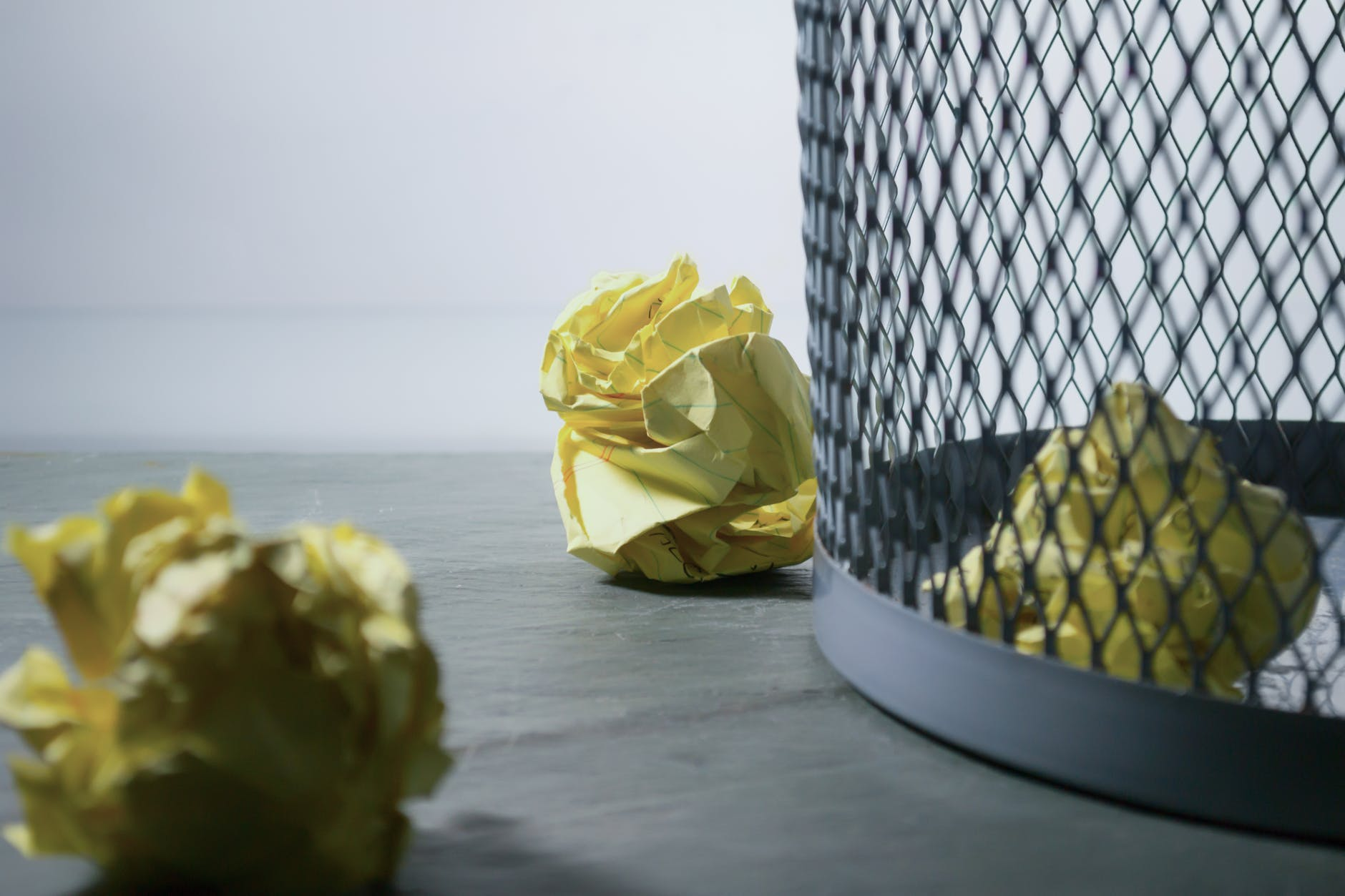 focus photo of yellow paper near trash can showing failure isn't real and that It's okay to feel unaccomplished
